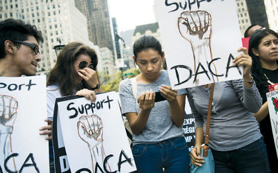 """""""Dreamers"""" originally from Ecuador, at a rally in Manhattan, watch Attorney General Jeff Sessions' remarks on ending the DACA program on September 5. (Drew Angerer/Getty Images)"""