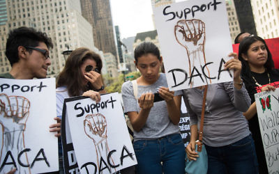 """""""Dreamers"""" originally from Ecuador at a rally in Manhattan watching Attorney General Jeff Sessions' remarks on ending the DACA program, Sept. 5, 2017. (Drew Angerer/Getty Images)"""