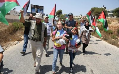 Palestinian demonstrators holding the Palestinian flag protest against the expansion of Jewish settlements in the West Bank village of Nabi Saleh, near Ramallah. August 07, 2015. Photo by FLASH90