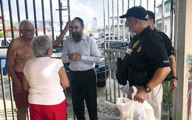 Rabbi Mendel Zarchi chats with San Juan residents after distributing a bag of relief goods.