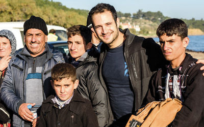 Yotam Polizer, second from right, stands with a family of Syrian refugees in Lesbos, Greece. (ISRAAID)