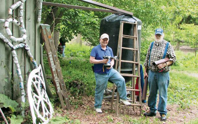 Amir Yechieli, left, and Jon Salamon install barrels at Teaneck Creek.