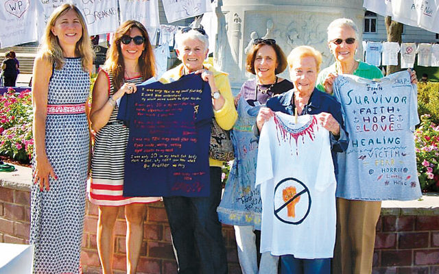 Christine Ordway and Helen Archontou, board member and CEO of the YWCA Bergen County, left, with NCJWBCS members Sue Kanrich, Bari-Lynne Schwartz, Estelle Greene, and Ilene Wechter at the YWCA Healingspace Clothesline Project. (Courtesy NCJWBCS)