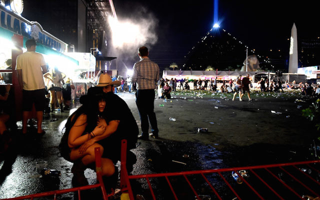 Concertgoers taking cover at a country music festival on the Las Vegas Strip following a mass shooting attack, Oct. 1, 2017. (David Becker/Getty Images)