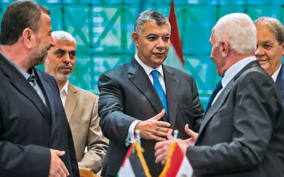 Hamas and Fatah leaders shake hands as they sign a reconciliation deal at Egyptian intelligence services headquarters in Cairo on October 12. (Khaled Desouki/AFP/Getty Images)