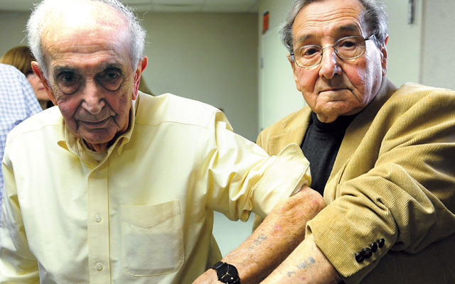 Walter Spier, left, and Werner Reich show the numbers the Nazis tattooed on their arms at Auschwitz. They are only 10 digits apart.