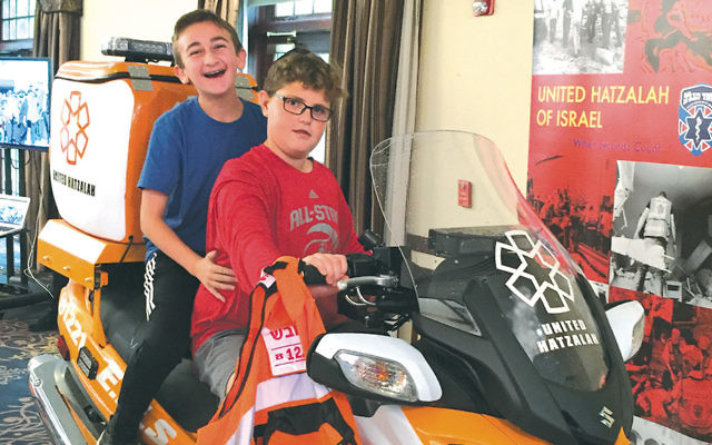 Temple Emanu-El religious school students Noah Parker and Isaac Wilk check out a United Hatzalah ambucycle at the Kesher Olam Expo. (Courtesy TE)