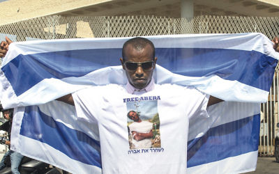 A relative, protesting in Israel on August 17, 2015, wears a shirt with a picture of Avraham Mengistu.  (Jack Guez/AFP/Getty Images)