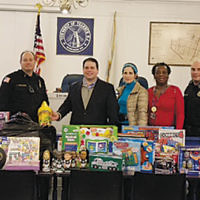 Members of the Teaneck Police Department flank, from left, Deputy Mayor Elie Y. Katz; Joy Sklar, chair of the Bergen County annual Chanukah Toy Drive; and Roz McLean, who works for Teaneck Township. The gifts are from the department's  toy drive. (Issa Abbasi)
