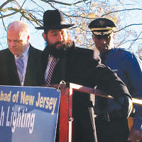Rabbi Avi Richler of Chabad of Gloucester County is joined by state Senate President Stephen M. Sweeney, left, and Maj. Brian Polite of the State Police at the 37th annual gathering of Chabad's New Jersey shluchim, where they lit the giant  menorah on the State House lawn in Trenton  for Chanukah. The candle-lighting, hosted by  the Rabbinical College of America, included  58 Chabad shluchim and many local dignitaries.