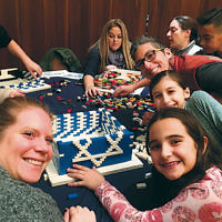 On December 17, members of Temple Beth Tikvah in Wayne, led by architect Stephen Schwartz, built a huge Chanukah menorah from Legos. Rabbi Meeka Simerly led attendees in song; dinner included latkes, chicken, and donuts. (Courtesy TBT)