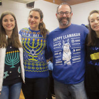 Students at the Bergen County High School of Jewish Studies celebrated Chanukah in school by eating sufganiyot, spinning dreidels, and wearing ugly Chanukah sweaters. Teacher Barnett Goldman joined BCHSJS students, from left, Brianna Leopold, Julia Holzsager, and Annabelle Simhon. (Courtesy BCHSJS)