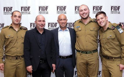 """Lior Raz and Avi Issacharoff of """"Fauda"""" are surrounded by IDF soldiers at the FIDF gala in Teaneck last week. (Courtesy FIDF)"""