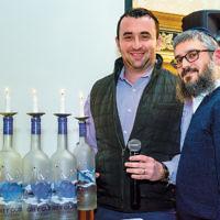 "Rabbi Mendel Zaltzman, right, and Arthur Ayzerov lit the menorah at Bris Avrohom of Fair Lawn's ""Dreidels & Drinks"" Chanukah party. (Courtesy BA)"