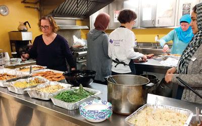 Sisterhood of Salaam/Shalom members prepare Christmas dinner for residents of the St. Paul's Men's Shelter in Paterson.