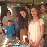 "Temple Beth El of Northern Valley held its 21st annual ""101 Menorahs"" Shabbat service on December 15. Families brought their own menorahs and candles to celebrate the fourth night of Chanukah and enjoyed a festive oneg Shabbat with latkes. (Courtesy TBENV)"