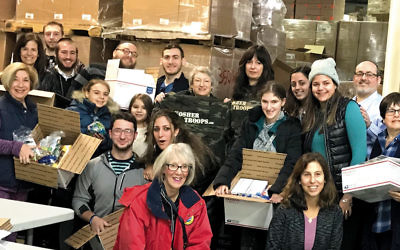 Volunteers from across the Jewish communities pause during their work in Mahwah warehouse.