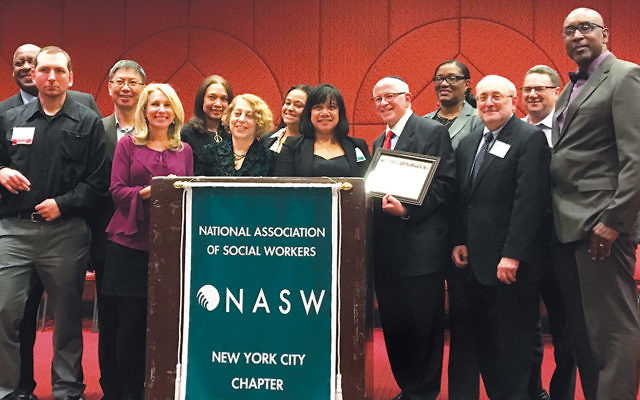 Dr. Steven Huberman of Teaneck, dean of the Touro College Graduate School of Social Work, holds his 2017 Top Social Worker Leader award, which he received at the annual National Association of Social Workers New York City chapter's Leadership Awards dinner. NASW-NYC chapter president Candida Brooks-Harrison stands behind him, along with Touro faculty, staff, students, and alumni. (Photos Courtesy Touro)