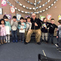 "Dick Burnon of Dumont, center, is surrounded by pre-schoolers at a Chanukah party with songs and refreshments at the Kaplen JCC on the Palisades in Tenafly. Burnon, known by the children as ""Grandpa B,"" has been an active member of the JCC's GrandFriends Program for four years.  (Ilene Conroy)"