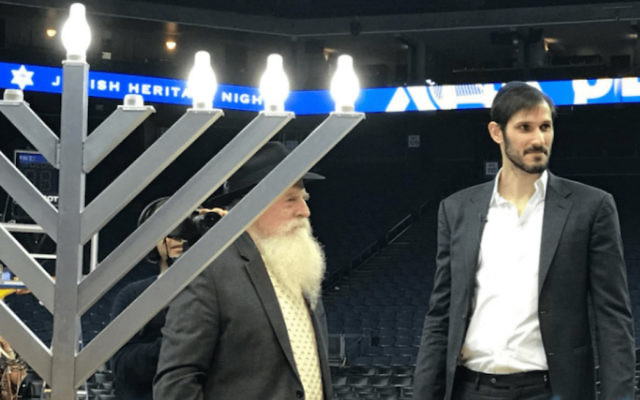 Israeli Golden State Warriors player Omri Casspi joins San Francisco Chabad Rabbi Yosef Langer to light the menorah after the Warriors beat Dallas on the team's annual Jewish Heritage Night, Dec. 14, 2017. (Courtesy of Golden State Warriors)