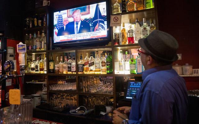 A patron at a Jerusalem pub watches as President Donald Trump recognizes the city as Israel's capital, Dec. 6, 2017. (Yonatan Sindel/Flash90)