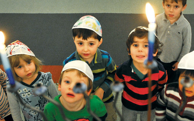 During Chanukah, Jewish preschoolers in Washington, D.C., gaze at a menorah. (Mark Gail/The Washington Post via Getty Images)