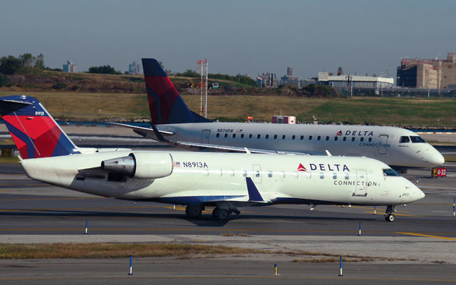 Two Delta Connection passenger jets sit on the runway at LaGuardia Airport. (Robert Alexander/Getty Images)