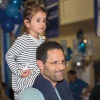 Another sits on her father's shoulders at last year's Israel celebration at the Kaplen JCC