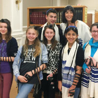 Religious school students at Shomrei Torah of Wayne don tefillin; they also do this weekly during Sunday school. (Courtesy Shomrei Torah)