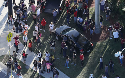 PARKLAND, FL - FEBRUARY 14:  People wait for loved ones as they are brought out of the Marjory Stoneman Douglas High School after a shooting at the school that reportedly killed and injured multiple people on February 14, 2018 in Parkland, Florida. Numerous law enforcement officials continue to investigate the scene.  (Photo by Joe Raedle/Getty Images)
