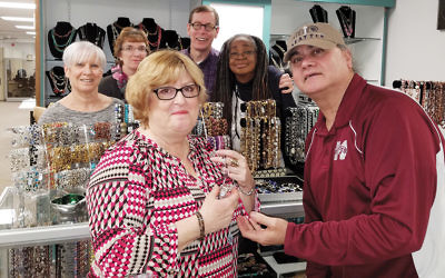 Adler Aphasia Center members Stacy Kaplan and Javed Ispahany show an item of jewelry that Ms. Kaplan designed. From left, Adler staff members Robin Strau and Tamara Heimlich – founding members of Team Teaneck – and Adler members Ken Albrecht and Denise Powlis-Lighty look on.