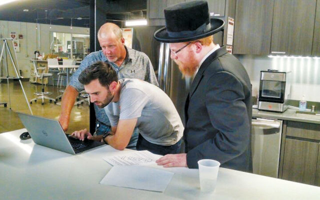 Rabbi Ortner works with engineers from GE.