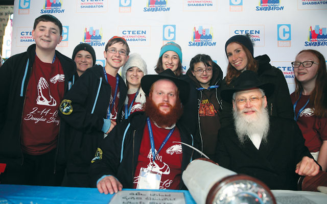 Rabbi Shaya Denburg, co-director of CTeen in Coral Springs, Fla., is joined by Rabbi Moshe Klein to his left; Chayale Denburg, co-director of CTeen in Coral Springs, Fla., standing and second from right, and survivors of the Parkland, Fla., school shooting. The survivors were in New York for Chabad's CTeen conference.