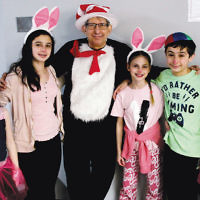 Rabbi Ronald Roth of the Fair Lawn Jewish Center/Cong. B'nai Israel with religious school students celebrating Purim at the shul's annual carnival.
