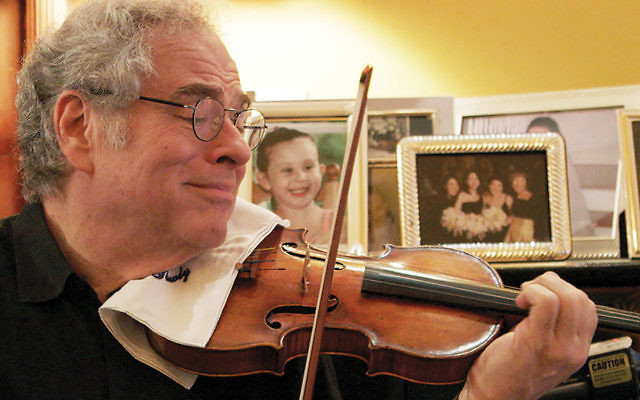 "Itzhak Perlman, shown in a scene from the documentary ""Itzhak,"" endured hardships to become arguably the most famous violinist in the world.  (Courtesy of Greenwich Entertainment)"