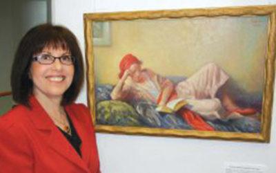 Miriam Friedmann Morris in front of a painting of Mathilde Friedmann