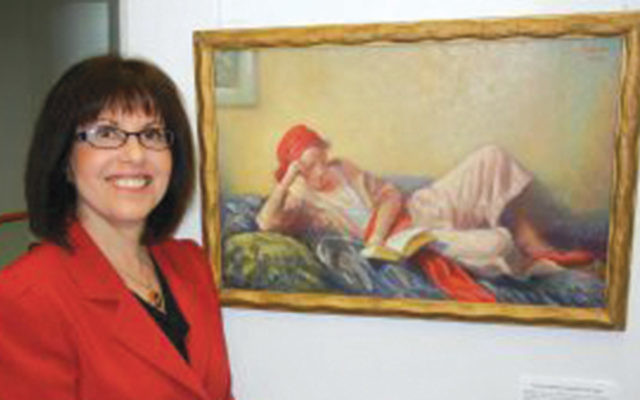 Miriam Friedmann Morris in front of a painting of Mathilde Friedmann