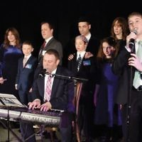Chazan Shim Craimer and his twin sons, Ben and Eli, perform, as Sinai families join them onstage.