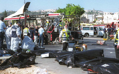 Israeli rescue workers stand over victims' bodies at the scene of a Palestinian suicide bombing on a passenger bus in Jerusalem on June 18, 2002.Yossi Zamir/Flash 90