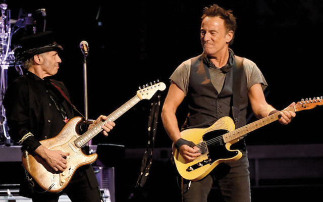 Nils Lofgren, left, on stage with Bruce Springsteen. (Kevin Winter/Getty Images)