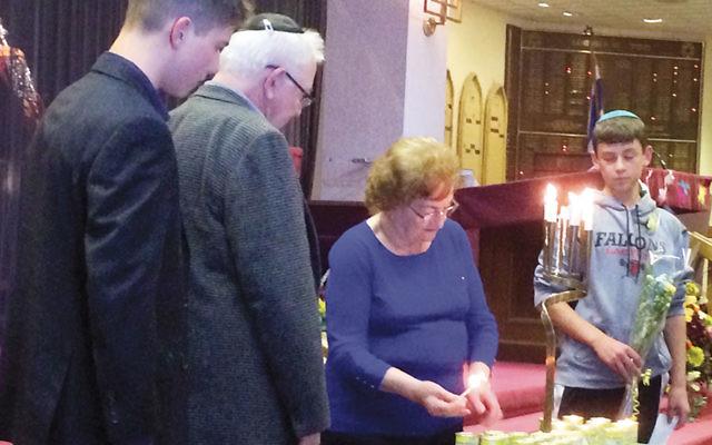 Three generations of the Rak family, Noah Rak, Sam Rak, and Miriam Rak, light a candle at last year's Holocaust commemoration. (Photo provided)