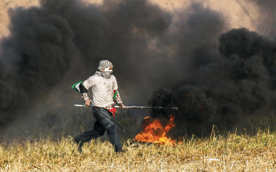 A Palestinian protester burns tires during clashes with Israeli forces near the security fence that separates Israel from Gaza on April 2, 2018. (Said Khatib/AFP/Getty Images)