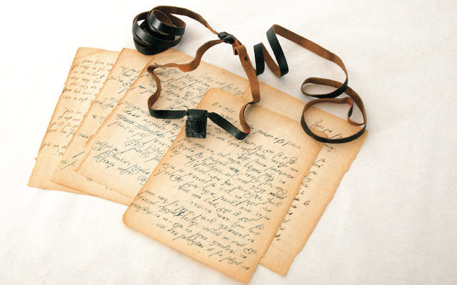 A set of tefillin and diary pages that belonged to Isaac Avigdor, a young Polish rabbi imprisoned at Mauthausen, are on display at the Amud Aish Memorial Museum. Avigdor shared the smuggled tefillin with other inmates during his imprisonment. (Courtesy of Amud Aish)