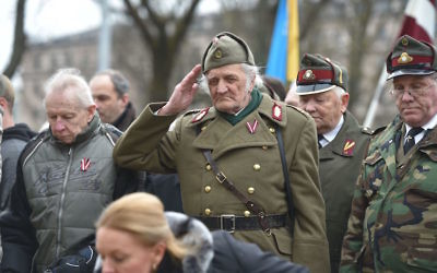 A man dressed in a pre-WWII Latvian military uniform salutes as former Nazi SS veterans and their sympathizers walk to the Monument of Freedom in Riga, March 16, 2016. (Ilmars Znotins/AFP/Getty Images)