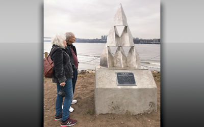 "Barbara Schaier-Peleg and Ephraim Peleg stand next to his sculpture, ""Sails,"" in its new home in Edgewater, overlooking the Hudson River."