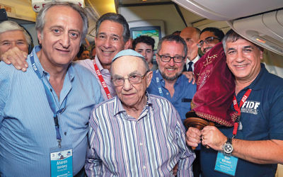 Aharon Steinberg of Ringwood, at left, and Holocaust survivor Leon Shear celebrate their bar mitzvah on the FIDF flight from Poland to Israel on April 16.