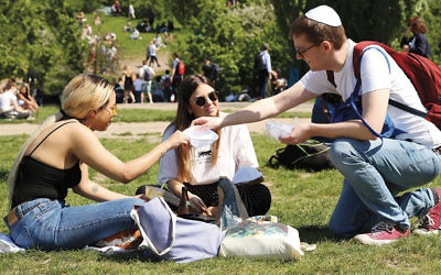 A volunteer hands out kippot to visitors at the Mauerpark in Berlin on April 29, 2018 to protest an anti-Semitic incident. (Adam Berry/Getty Images)