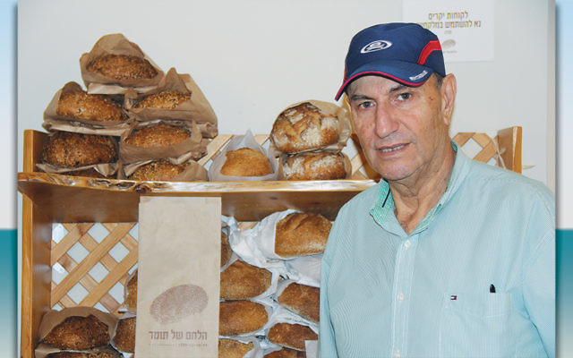 Yehezkel Balas, a building contractor who lives in Arnona, said the embassy will bring more traffic, higher rents, and more business to the neighborhood. He's standing in his son's bakery. (Photos by Ben Sales)