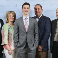 Honoree Mitchell Bloom, center, flanked by his parents, Joyce and Eric Bloom; his brother, Evan, left, and grandfather, Marty Weintraub, right.