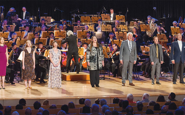 """Ellis Island cast of actors, from left, Lesley Fera, Samantha Sloyan, Kira Sternbach, Camryn Manheim, Barry Bostwick, Lucas Near-Verbrugghe, and Michael Nouri on stage for Pacific Symphony's """"Ellis Island: The Dream of America"""" by composer Peter Boyer. (Joshua Sudock)"""